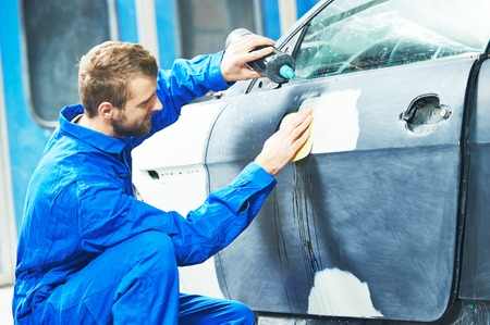 polisher: auto mechanic worker applying washing car body preparing for painting at automobile repair and renew service station Stock Photo