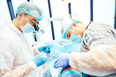 odontologa: Dos dentista hombre en uniforme efectuar operación implante dental en un paciente en el consultorio dental
