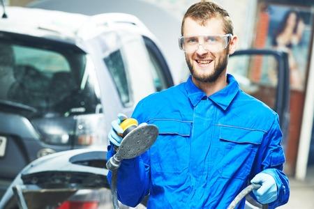 mecanico: retrato de la sonrisa trabajador mec�nico de autom�viles con la m�quina pulidora de energ�a en la reparaci�n de autom�viles y renovar la estaci�n de servicio