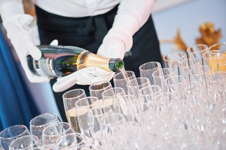 coctail: Waiter bartender pouring red wine into glasses at party event