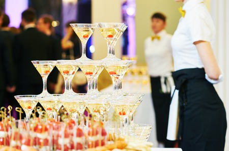 Champagne pyramid with waitress on event, party or wedding banquet reception Фото со стока
