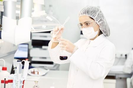 laboratorio clinico: Farmacéutica investigadora científica en uniformes de protección verter frasco con solución líquida en el laboratorio de la farmacia