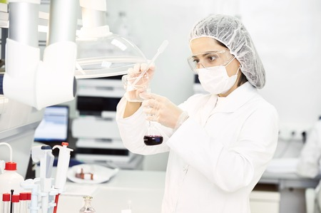 Pharmaceutical scientific female researcher in protective uniform pouring flask with liquid solution at pharmacy laboratory