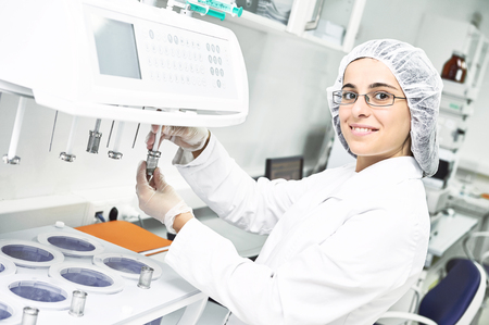Pharmaceutical scientific female researcher in protective uniform working with dissolution tester at pharmacy industry manufacture factory laboratory Foto de archivo