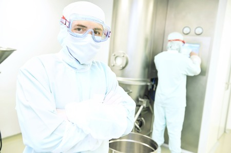pharma: Portrait of pharmaceutical factory worker in protective uniform standing in front of pharma granulator dryer and fluid bed system at pharmaceutical factory Stock Photo