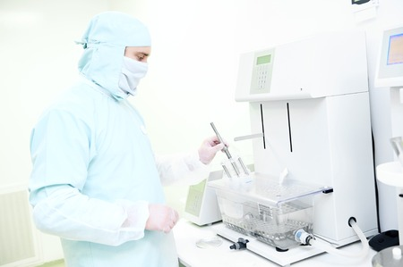 disintegration: Pharmaceutical scientific male researcher in protective uniform working with disintegration tester at pharmacy industry manufacture factory laboratory. Worker holding basket rack assembly in his hand.