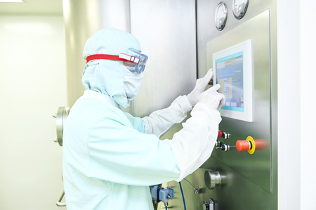experienced operator: Pharmaceutical industry. Pharmaceutical factory worker operating pharma granulator dryer and fluid bed system at pharmaceutical factory