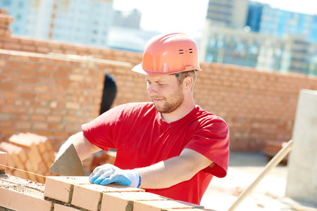 building wall: construction worker. Portrait of mason bricklayer installing red brick with trowel putty knife outdoors Stock Photo