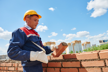 brick mason: construction worker. mason bricklayer installing red brick with trowel putty knife outdoors