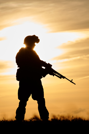 soldiers: military. soldier silhouette in uniform with machine gun or assault rifle at summer evening sunset