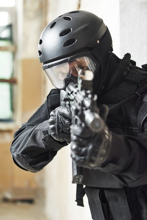 special agent: Military industry. Special forces or anti-terrorist police soldier, private military contractor armed with with machine gun ready to attack during clean-up operation
