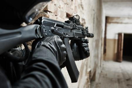 soldado: industria militar. fuerzas especiales o soldado de la policía antiterrorista, contratista privado armados con fusil de asalto listo para atacar durante la operación de limpieza, la misión