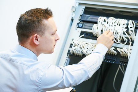service engineer: Networking service. network engineer administrator checking server hardware equipment of data center Stock Photo