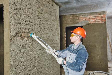 pulverizador: Yesero operación de la máquina equipo pulverizador para pulverizar en capa fina de masilla de acabado de yeso en la pared de ladrillo