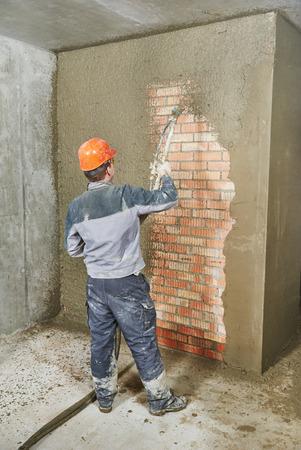 cemento: Yesero operación de la máquina equipo pulverizador para pulverizar en capa fina de masilla de acabado de yeso en la pared de ladrillo