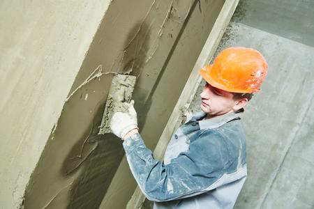 hombres trabajando: Construcción yesero trabajador con la paleta enyesado de una pared Foto de archivo