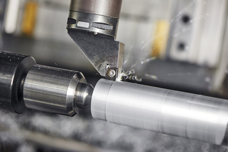 machine tool: metalworking  industry: cutting steel metal shaft processing on lathe machine in workshop. Selective focus on tool Stock Photo