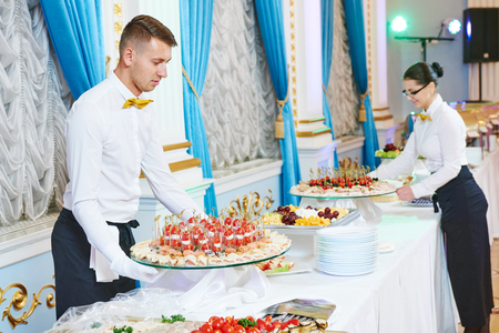 waitress occupation. Young woman with food on dishes servicing in restaurant during catering the event Stock Photo - 49831372