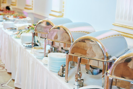 catering service. Metal buffet heated trays with food on tabeles at banquet event celebration