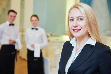 hotel staff: Catering services. Restaurant manager portrait in front of waitress and waiter staff at banquet hall