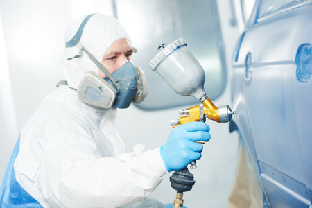 priming paint: automobile repairman painter in protective workwear and respirator painting car body bumper in paint chamber Stock Photo