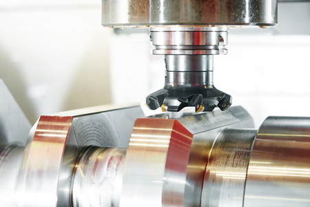 milling center: cnc metal working machining center with cutter tool during metal detail milling at factory. Authentic shooting in challenging conditions.