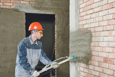 leveling: Plasterer operating sprayer equipment machine for spraying thin-layer putty plaster finishing on brick wall