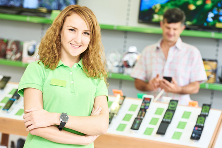 electronic store: Portrait of young happy female seller assistant  in electronics retail store