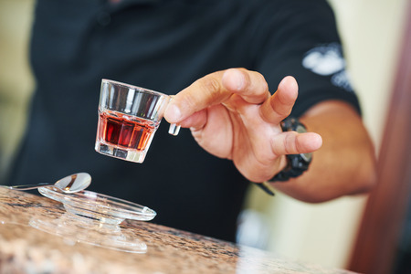 spirituous beverages: sommelier barman hand holding a little wine glass with alcohol aperitif liquor Stock Photo