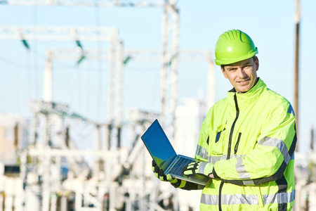 service engineer: Engineering supervision. Portrait of male service engineer in high visibility reflecting clothing and hard hat working on notebook computer at heat electropower station Stock Photo