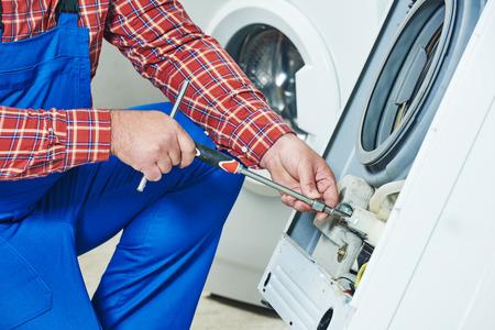 servicio domestico: Lavadora de reparaci�n. manos del reparador con destornillador de desmontar la unidad da�ada para su reparaci�n