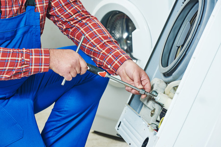 Waschmaschine zu reparieren. Reparateur Hände mit Schraubendrehers beschädigt Gerät zur Reparatur