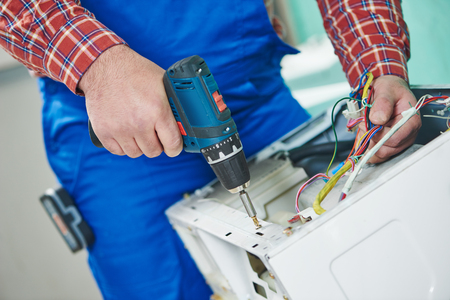 repairer: Washing machine repair. Repairer hands with screwdriver disassembling damaged unit for repair