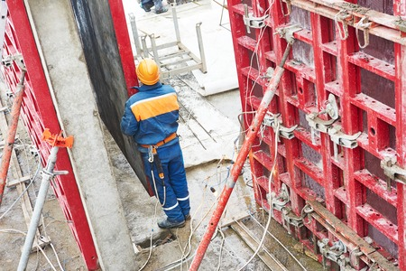 rigger: Construction builder worker disassemble falsework construction at building site Stock Photo