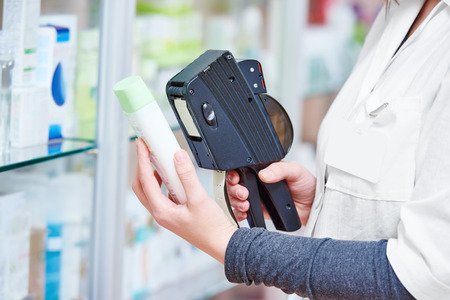 Hand of female pharmacist using labeling gun labeler for sticking price label of medicine in in drugstore Stock Photo