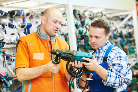 Vertriebsassistentin bei der Arbeit. männlich Baumarkt Arbeiter hilft, Bohrer oder Perforator an Käufer Kunde wählen