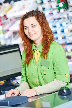 check out: supermarket cashier worker at check out cashdesk in shop store