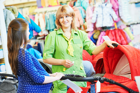shopping buggy: Pregnancy shopping. Female saleswoman selling perambulator for baby carriage to young pregnant woman at shop store Stock Photo