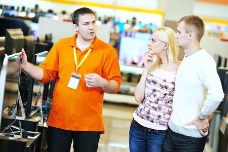 Familia joven eligiendo televisor con dependienta en electrodomésticos supermercado centro comercial