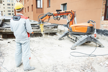 protective equipment: builder worker in safety protective equipment operating construction demolition machine robot. Focus on tool