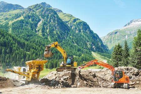 excavatrice charge le sol dans la machine en pierre de concassage au cours de terrassement travaille en plein air au montagnes chantier de construction