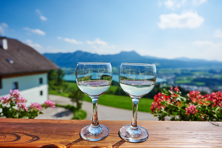 austrian village: Two glasses with white wine in front of austrian village and alpine mountains on wooden table