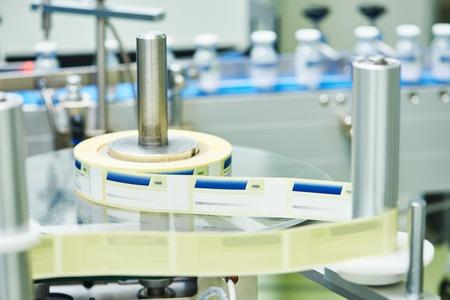 industria quimica: industria farmacéutica. Las botellas de vidrio ampollas pasar por la máquina de etiquetado en la farmacia fábrica de la fabricación