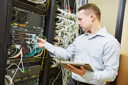 database server: Networking service. network engineer administrator checking server hardware equipment of data center Stock Photo