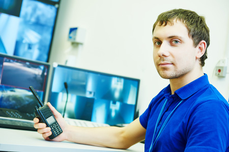 police radio: security guard officer with portable radio transmitter over video monitoring surveillance security system