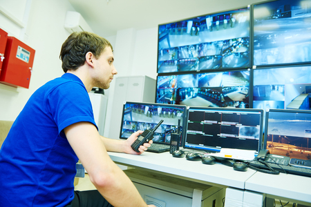 security monitoring: security guard officer watching video monitoring surveillance security system Stock Photo