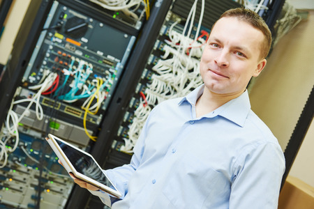 Networking service worker portrait. network engineer administrator with tablet computer checking server hardware equipment of data center