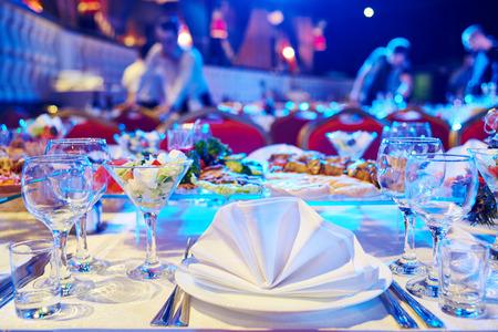 Catering-Service. Restaurant gedeckten Tisch mit Essen zu Fall. Natürliche authentische Schuss unter schwierigen Lichtverhältnissen.