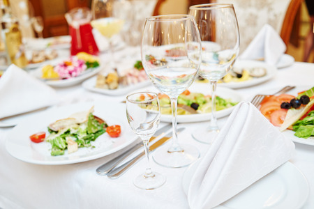 restaurant dining: Catering service. Restaurant set table with food at event. Natural authentic shot in challenging light condition.