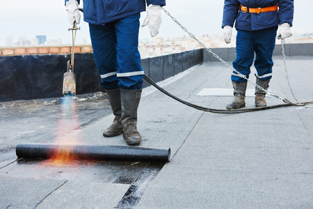 Flat roof installation. Heating and melting bitumen roofing felt by flame torch at construction site Foto de archivo